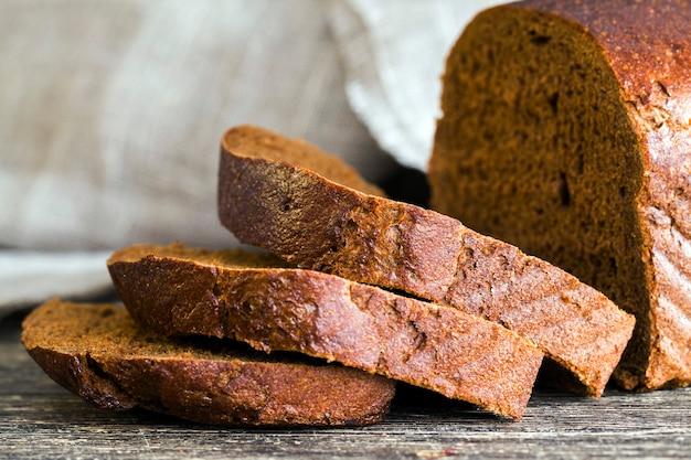 Черный горький хлеб из ржаной муки, крупный план еды на кухонной разделочной доске
