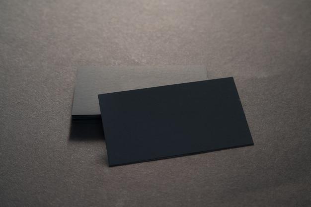 Черные пустые визитные карточки на черной поверхности.