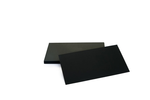 Black blank business cards on a white surface.