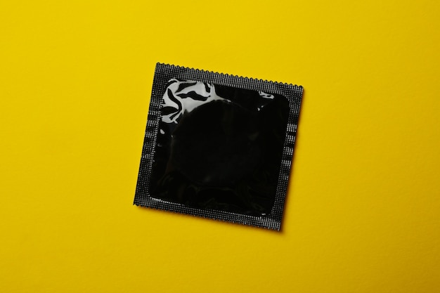 Black blank condom on yellow surface