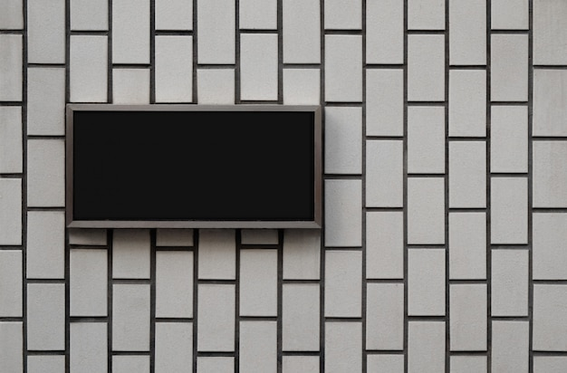 Black blank signage board on vintage wall texture