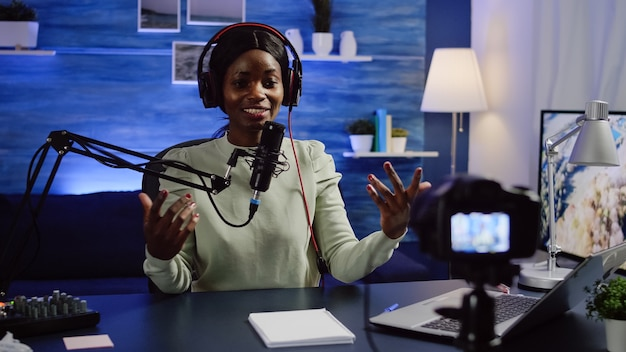 Black blogger influencer recording video blog concept waving and speaking looking at camera on tripod in home podcast studio