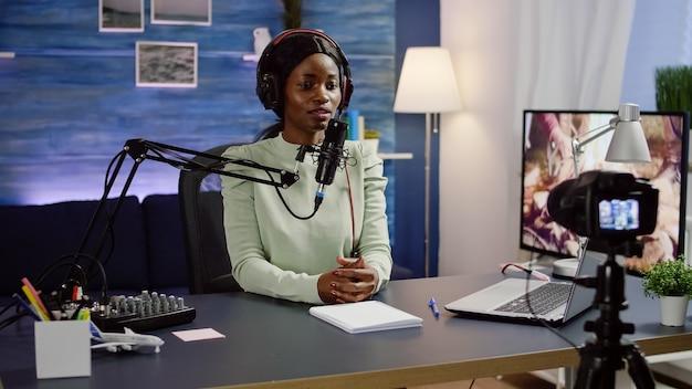 비디오 카메라가 새로운 팟 캐스트를 녹화하는 동안 집에 앉아있는 블랙 블로거