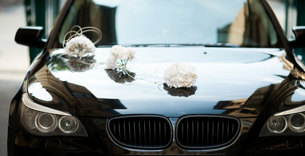 Black bmw decorated with white wedding bouquets