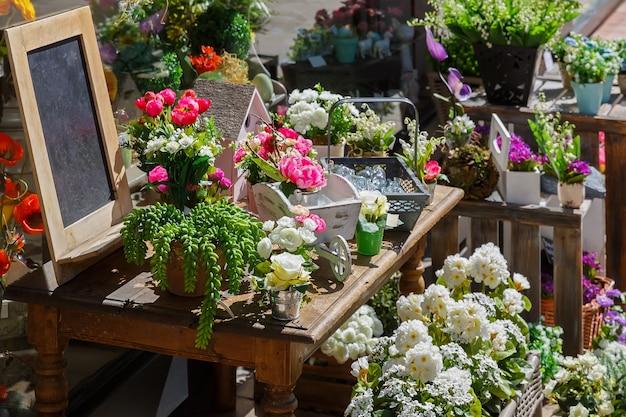 Черная доска и цветы стоят на столе на уличной распродаже