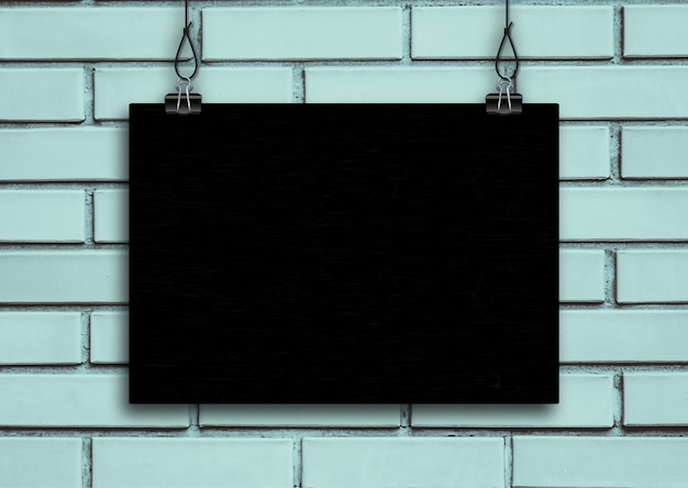 Black board on blue brick wall background.