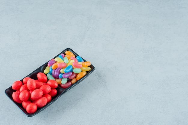 Una lavagna piena di caramelle colorate di fagioli su una superficie bianca