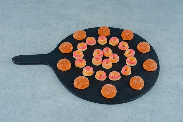 A black board full of round orange jelly sweets in the shape of rings and orange jelly candies with sugar