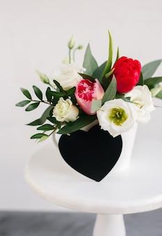 Черная доска copyspace сердца. весенний букет в белой вазе на деревянной белой подставке. розы, тюльпаны и лизиантус.