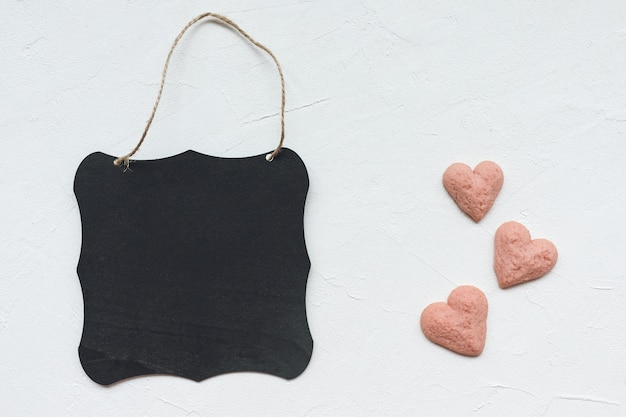 Black board and heart shaped cookies on a white background