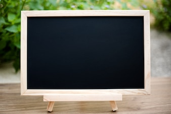 Black board on wood table top with sun and blur green tree bokeh background,