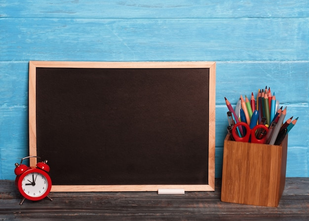 Black board, pencils, cloak, chalks on wooden table