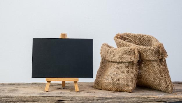 블랙 보드 스탠드와 흰색 배경 위에 절연 복사 공간 그런 지 나무 선반에 두 개의 다른 크기 삼 베 가방