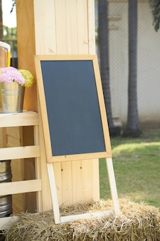 Black board stand on straw decorate with flowers vase