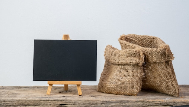 Black board stand and two different size burlap bags on grunge wooden  shelf with copy space isolated over white background