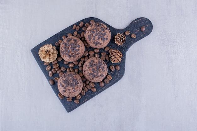 Черная доска с кофейными зернами, печеньем и сосновыми шишками на белом фоне.