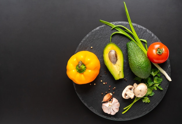 신선한 다채로운 원시 달콤한 고추, 아보카도 배, 봄 양파, 파슬리, 마늘, 토마토가 들어간 블랙 보드