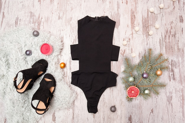Black body, shoes and  decorated fir branch on wooden background