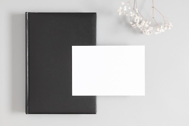 Black book cover with blank card and dried flowers on a white background