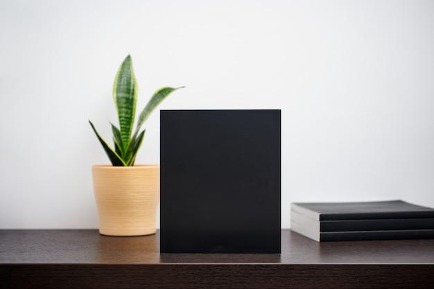 Макет черной книги с кактусом в горшке на темном рабочем столе и белом фоне стены