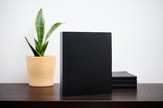 Black book mockup wtih cactus in a pot on dark workspace table and white wall background