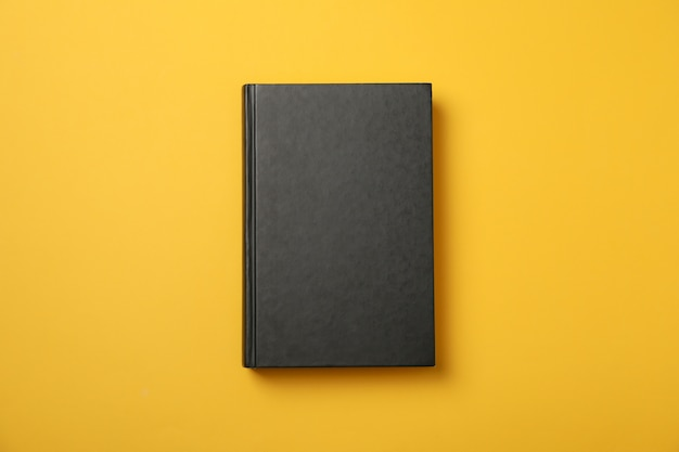 Black book on yellow space, space for text