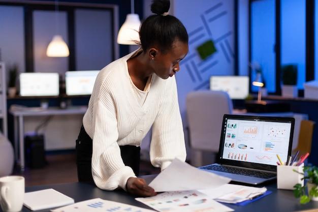 통계 그래프를 확인하는 재무 보고서를 작성하는 흑인 회계사, 노트북을 보고, 마감 시간을 준수하기 위해 초과 근무를 하는 시작 사무실에서 늦은 밤 책상에 서 있는 숫자를 가리키는
