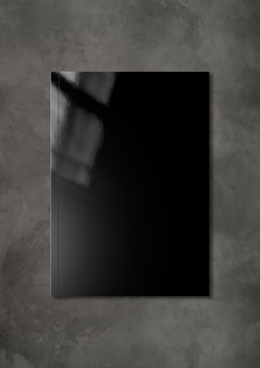 어두운 콘크리트 배경에 고립 된 검은 책자 표지