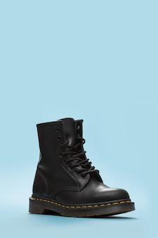 Black boot on the blue background . fashion shoes still life. classic unisex black lace-up fashion combat boot. close up view of boot with copy space for text
