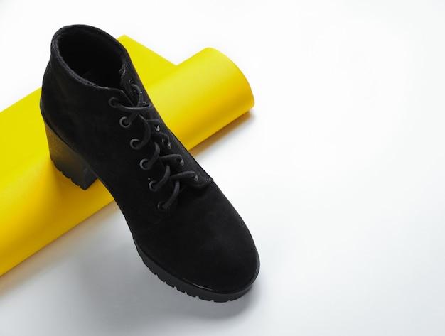 黄色い紙のロールアップロールに黒のブーツ