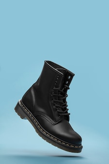 Black boots in the air on the blue background .