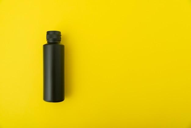黄色の背景に黒いボトルバイアル。スペースをコピーします。モックアップ。