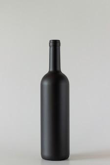 Black bottle of wine on a grey background.