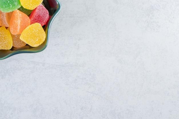 Ciotola nera di marmellate di gelatina colorate su sfondo marmo.
