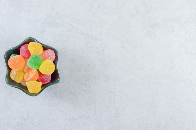 Black bowl of colorful jelly marmalades on marble.