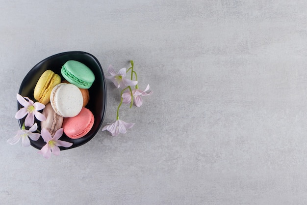 Black bowl of colorful sweet macaroons with flowers on stone table.