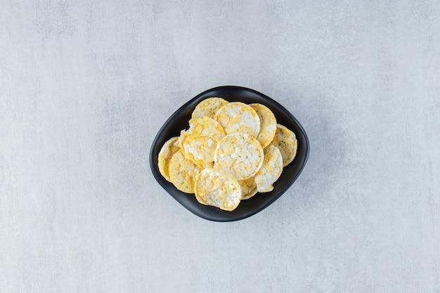 Ciotola nera di deliziose patatine di riso su pietra.