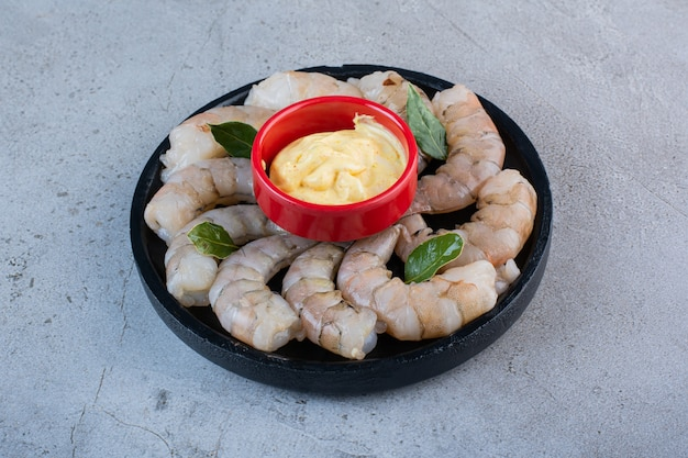 A black bowl of delicious shrimps with mustard on a stone background .