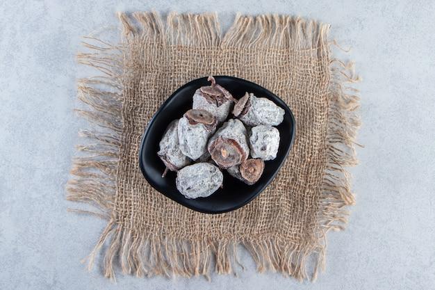 Ciotola nera di frutti di cachi secchi su sfondo marmo.