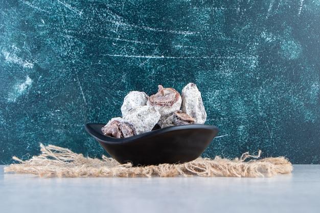 Ciotola nera di frutti di cachi secchi su marmo.