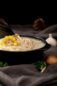 Black bowl filled with noodle soup and corn on a grey cloth with garlic and mushrooms