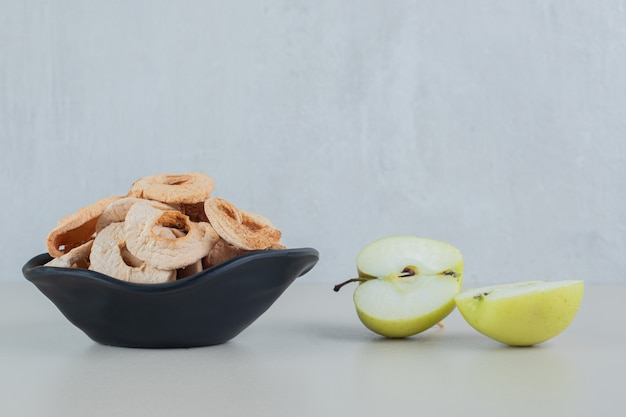 A black bowl full of dried apple fruit with slices of fresh apple .