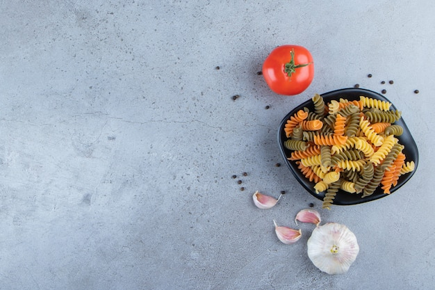 A black bowl full of multi colored macaroni with fresh red tomato and garlic on a stone background .