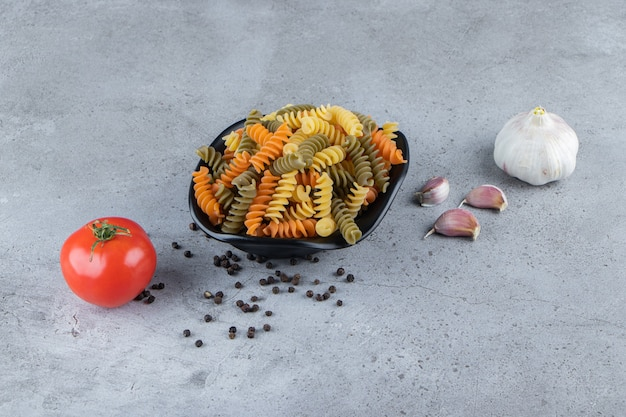 A black bowl full of multi colored macaroni with fresh red tomato and garlic on a stone surface .