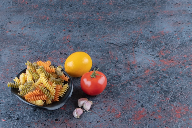 A black bowl full of multi colored macaroni with fresh red tomato and lemon on a dark background .
