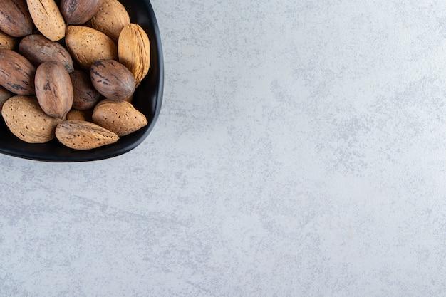 Черная чаша, полная очищенного миндаля и грецких орехов на каменном фоне.