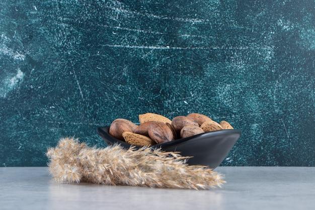 Ciotola nera piena di mandorle sgusciate e noci su fondo di pietra.