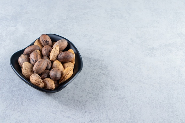 Ciotola nera piena di mandorle sgusciate e noci su pietra.