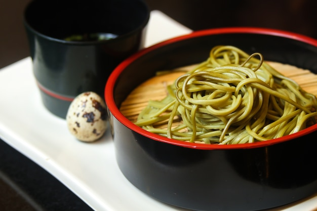 Black bowl of green noodles with quail egg and a sauce served on a white tray