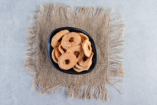 Ciotola nera di anelli di mela essiccati sani sulla pietra.